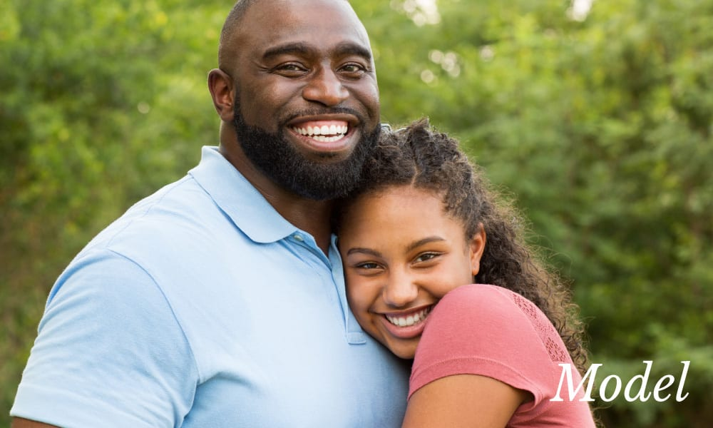 Father with Large Smile Hugging Young Daughter