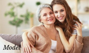 Grandmother and Granddaughter Embracing On Couch