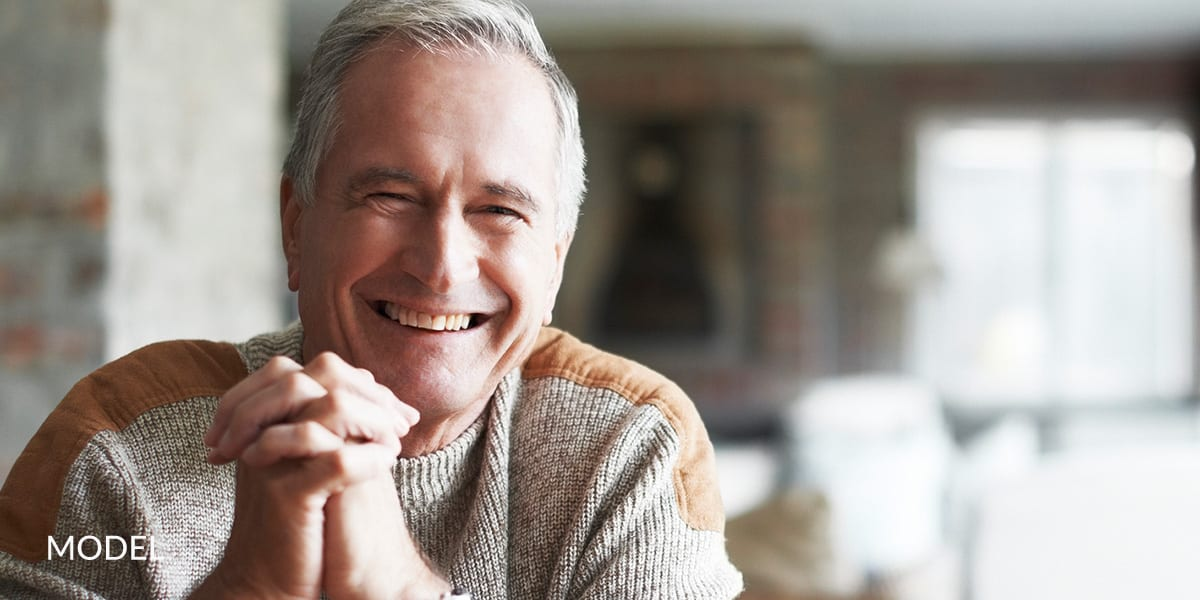 Older Man Smiling And Clasping Hands