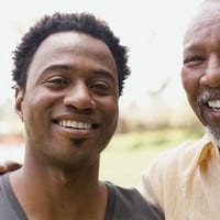 Young Smiling Man Next to Father