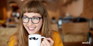 Smiling Young Female with Glasses Holding Mug With a Mustache